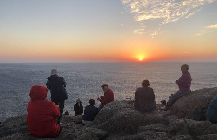 Pilger auf den Felsen bei Sonnenuntergang am Kap Finisterre
